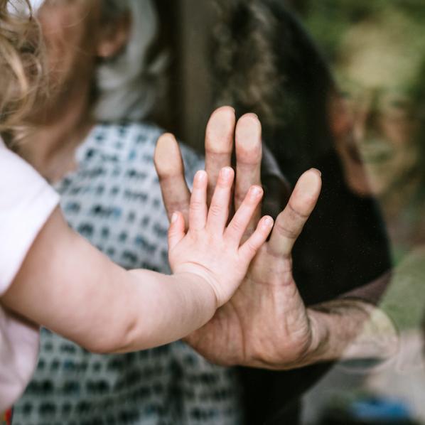 Main d'une petite fille contre la main d'un senior.