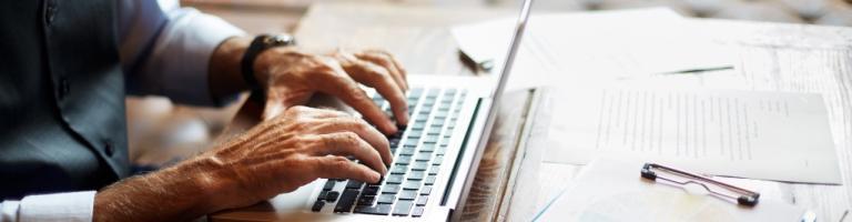 Senior remplissant le formulaire APA en ligne depuis un ordinateur