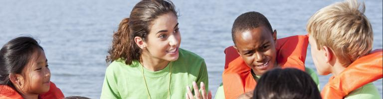 Jeune femme expliquant les consignes de sécurité pour pratiquer le kayak à des enfants.