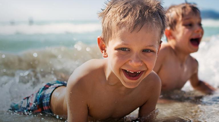 Deux enfants jouant dans l'eau au bord de la mer